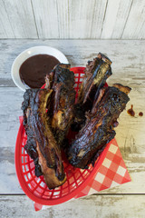 Barbecued ribs in red basket with sauce top view