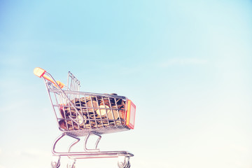 Miniature supermarket shopping cart filled with golden coins against blue sky, color toning applied.