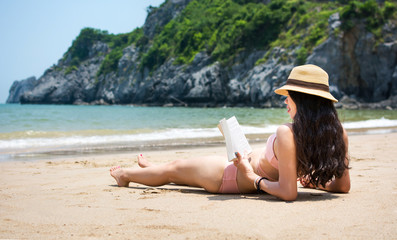 Girl reading book and sunbathing on the beach