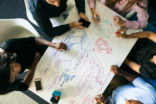 Workspace: Overhead View As Diverse Team Writes Out Plans