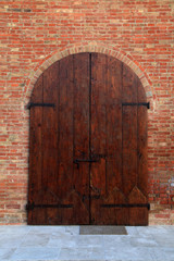 Old wooden gate in brick house, Italy