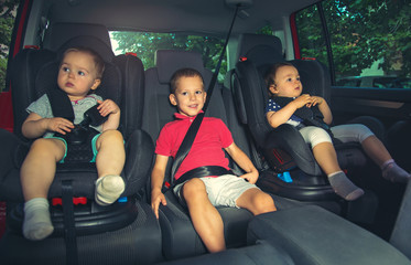 Three children in car safety seat - family, transport, safety, road trip and people concept Wall mural