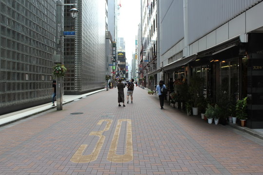 People walking on the street in tokyo near to maison hermes by renzo piano architecture
