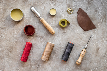 Leather workshop. Tanner's tools on grey stone background top view