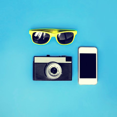 Colorful fashion set - retro camera, screen smart phone with yellow a sunglasses over blue background