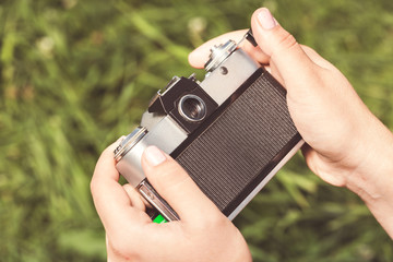 Woman hands are holding old vintage film camera outdoors. Toned.