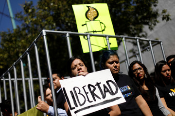 A member of Amnesty International holds sign next to a mock prison cell during a demonstration against the human rights abuses, demanding the release of activists arrested in Turkey, outside the Turkey's Embassy in Mexico City