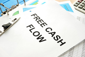 Stack of papers with title free cash flow (FCF) or free cash flow to firm (FCFF).