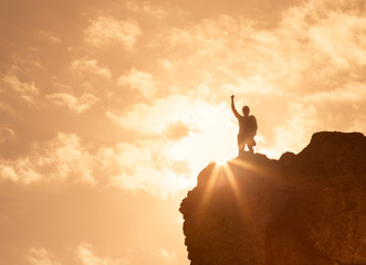 Success, victory and adventure! Man standing on top a mountain with arms up in the air.