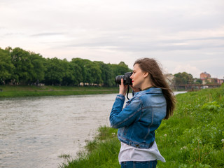 Beautiful girl tourist in a cotton jacket taking photos with a professional camera on the banks of the river in windy weather