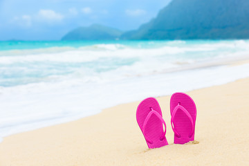 Beach holiday concept. Pair of colorful sandals on a tropical beach. (location Hawaii)
