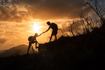People helping each other. Team work. Hikers climbing up a mountain.