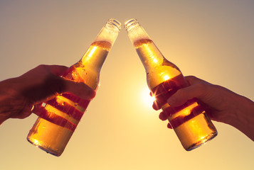 Silhouette of hands toasting bottle of beer outdoors.