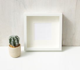 Blank photo frame with cactus plant, home decor.