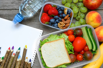 school lunch boxes with sandwich, fruits, vegetables and bottle of water with colored pencils