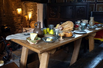 Rustic old wooden dining table in a medieval cottage, laid with bread, meat, cheese and fruit, and antique pottery and pewter