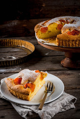 Homemade autumn and summer baked pastries. Sponge cake with apricots. Cut into pieces, plate, fork. On the stand. On the old wooden rustic table. Copy space