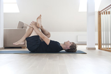 Man stretching thighs on yogamat