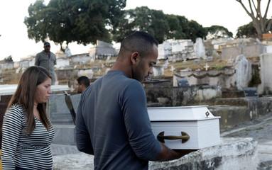 Cosme carries the coffin of his son during his funeral at a cemetery in Duque de Caxias near Rio de Janeiro