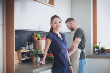 Couple drinking wine while cooking in the kitchen