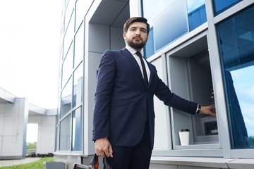 The businessman withdraws money from the ATM