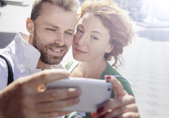 Smiling man and woman taking picture of themselves on cellphone, background of street. Day, outdoor