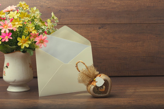 Heart-shaped gift with yellow invitation card and flower vase