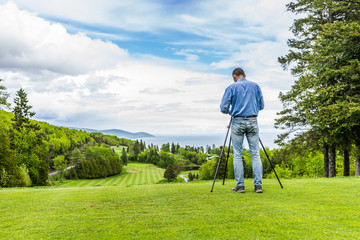 Landscape view of green golf course with hills in summer in La Malbaie, Quebec, Canada in Charlevoix region with photographer and tripod