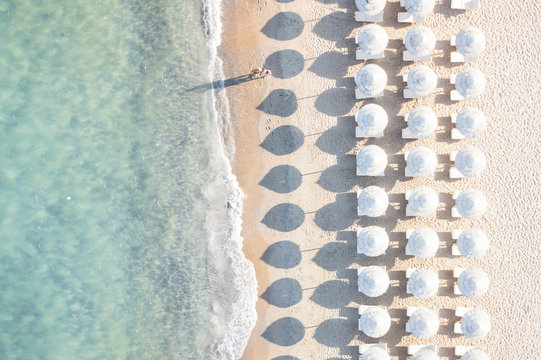 Aerial view of white beach, umbrellas and turquoise clear water during sunset, Mediterranean sea, Sardinia, Italy,