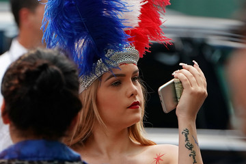 A so-called Desnuda, a woman with painted naked body parts that poses for photos for tips, looks at her reflection in her phone in Times Square in New York City