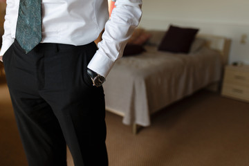 Businessman in white shirt holding hands with watches in the pockets of black trousers in an hotel room before an important meeting. Serious handsome man in casual white shirt, black tie, black pants.