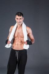 Strong athletic man standing on black background.