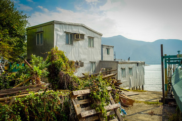 Metallic building used as home in old fishermen village Tai ,with a lake in the horizont, in Hong Kong