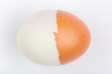 Half peeling of hard shell boiled egg isolate on white background.
