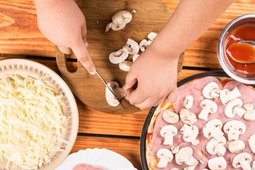Slicing mushrooms and preparing ingredients for baking pizza