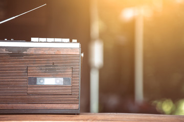 Retro radio cassette stereo on wooden table in vintage color tone