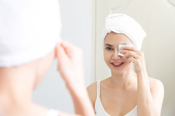 Healthy fresh girl removing makeup from her face with cotton pad. Skin care and beauty concept.