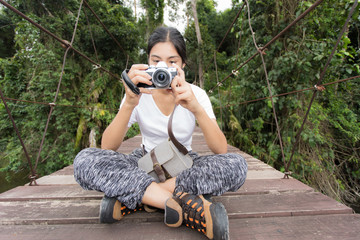 Asian woman taking photos outdoors in a forest