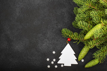 New Year's festive decorations with fluffy fir branches with young green cones, with Christmas tree decorations on a dark background. Top View.
