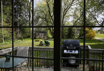 A lawnmower and barbeque are seen through the kitchen window of a house for sale in Hamilton