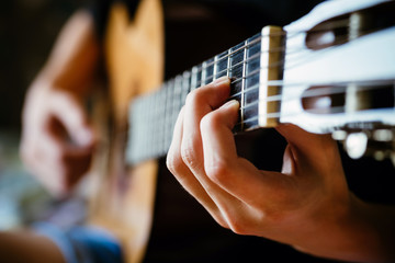 young musician playing acoustic guitar, live music background