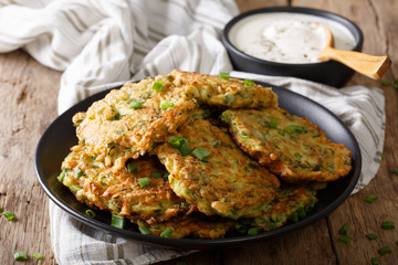 Fritters with zucchini and green onion, sour cream close-up. horizontal