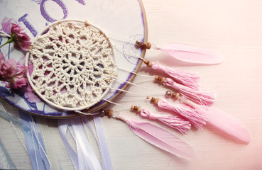 Dreamcatcher with pink feathers and roses on a wooden background.