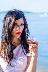 Elegant woman relax with glass of wine on a embankment and thinking about something. Problem of women alcoholism