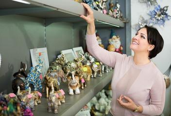 Mature woman near souvenirs shelves