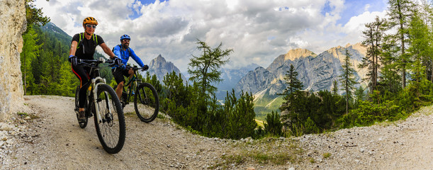 Wall Mural - Mountain biking couple with bikes on track, Cortina d'Ampezzo, Dolomites, Italy