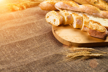 still life with French fresh bread baguettes with poolish on a wooden cutting board and wheat in rays of the sun. Shallow dof, copyspace for text