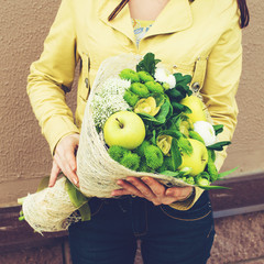 woman received trendy original greenery bouquet made with green and white flowers, apples wrapped in paper. For Valentines Day, Birthdays and Mothers Day, toned image