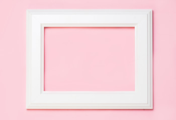 White wooden frame on pink background, free space for your text. top view, flat lay