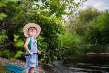 The grandson is fishing with his grandmother on the river bank. Fishermen with a fishing rod in the summer. A little boy with a mother puts a bait on a fishing rod, holds a fish, spend time together